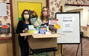 Staff holding Book Depot book donations